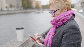 Mujer que usa smartphone en el río almacen de video