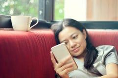 Mujer que usa smartphone en el sofá Fotografía de archivo libre de regalías