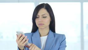 Mujer que usa smartphone en el trabajo para hojear almacen de video