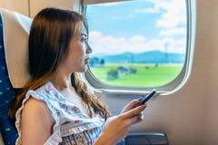 Mujer que usa smartphone en el tren fotografía de archivo libre de regalías