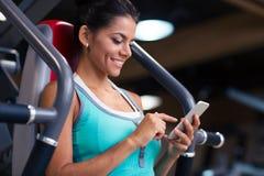 Mujer que usa smartphone en gimnasio de la aptitud Foto de archivo