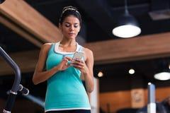 Mujer que usa smartphone en gimnasio de la aptitud Fotografía de archivo libre de regalías