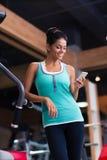 Mujer que usa smartphone en gimnasio de la aptitud Fotos de archivo