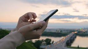 Mujer que usa smartphone en la ciudad después de puesta del sol metrajes