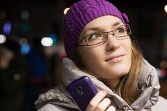 Mujer que usa smartphone en la ciudad por noche Imagen de archivo libre de regalías