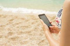Mujer que usa smartphone en la playa Fotos de archivo