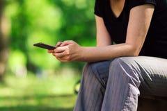 Mujer que usa smartphone en parque público Fotos de archivo libres de regalías