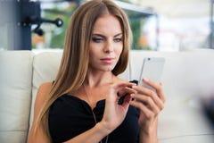 Mujer que usa smartphone en restaurante Imagenes de archivo