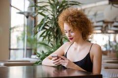 Mujer que usa smartphone en restaurante Imagen de archivo