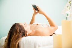 Mujer que usa smartphone en un balneario Imagen de archivo libre de regalías