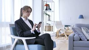 Mujer que usa Smartphone, hojeando en línea en el trabajo almacen de video
