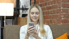 Mujer que usa Smartphone, interior, joven, almacen de metraje de vídeo