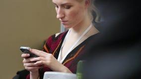 Mujer que usa smartphone móvil La muchacha sostiene un teléfono móvil metrajes