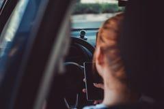 Mujer que usa smartphone m?vil mientras que conduce peligro y el riesgo de accidentes fotografía de archivo