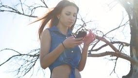 Mujer que usa smartphone Medios sociales de la muchacha en Internet en smartphone del aire libre almacen de video