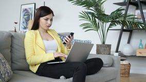 Mujer que usa Smartphone, ojeada en línea mientras que se sienta en el sofá almacen de metraje de vídeo