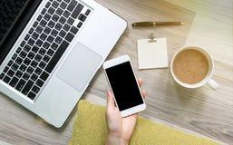 Mujer que usa smartphone y el ordenador portátil en piso de madera Imagenes de archivo