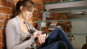 Mujer que usa Smartwatch para hojear, el correo electrónico y los mensajes metrajes