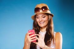 Mujer que usa SMS o mandar un SMS de la lectura del teléfono móvil Foto de archivo libre de regalías