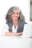 Mujer que usa su computadora portátil Foto de archivo