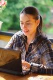 Mujer que usa su computadora portátil al aire libre. Fotografía de archivo