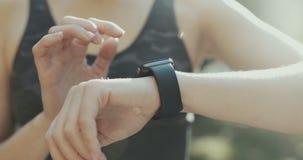Mujer que usa su dispositivo usable de la tecnología de la pantalla táctil del smartwatch en luces de la mañana metrajes