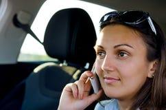 Mujer que usa su móvil en un coche imágenes de archivo libres de regalías