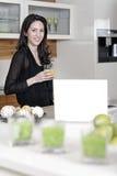Mujer que usa su ordenador portátil en cocina Imagenes de archivo