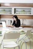 Mujer que usa su ordenador portátil en cocina Fotos de archivo libres de regalías