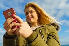 Mujer que usa su smartphone afuera, día soleado Imagenes de archivo