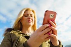 Mujer que usa su smartphone afuera, día soleado Foto de archivo libre de regalías
