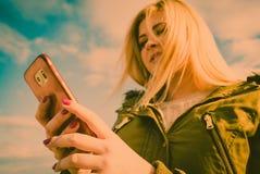 Mujer que usa su smartphone afuera, día soleado Fotos de archivo