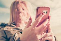 Mujer que usa su smartphone afuera, día soleado Fotografía de archivo