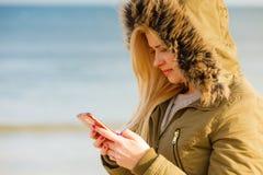 Mujer que usa su smartphone afuera, día soleado Imagen de archivo libre de regalías