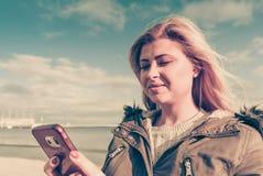 Mujer que usa su smartphone afuera, día soleado Fotografía de archivo libre de regalías