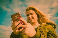 Mujer que usa su smartphone afuera, día soleado Imagen de archivo