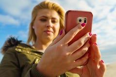 Mujer que usa su smartphone afuera, día soleado Foto de archivo