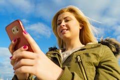 Mujer que usa su smartphone afuera, día soleado Fotos de archivo libres de regalías
