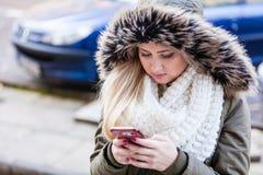 Mujer que usa su smartphone afuera en día frío Imagenes de archivo