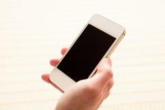 Mujer que usa su smartphone dentro Imagen de archivo libre de regalías