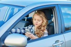 Mujer que usa su smartphone mientras que conduce un coche Fotografía de archivo