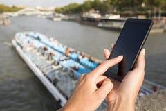 Mujer que usa su teléfono celular, fondo París Imágenes de archivo libres de regalías