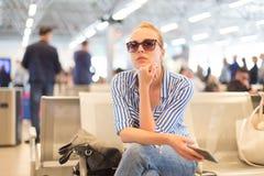 Mujer que usa su teléfono celular mientras que espera para subir a un avión en las puertas de salida en el aeropuerto internacion foto de archivo libre de regalías