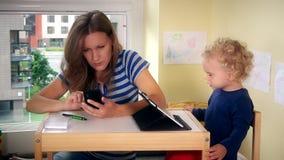 Mujer que usa su teléfono elegante y ayudando a la muchacha del niño que juega con la tableta metrajes