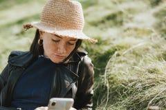 Mujer que usa su teléfono en un parque imagen de archivo libre de regalías