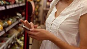 Mujer que usa su teléfono mientras que compras almacen de metraje de vídeo
