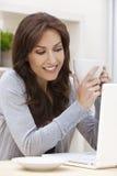 Mujer que usa té o el café de consumición del ordenador portátil Fotografía de archivo libre de regalías