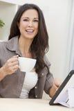 Mujer que usa té o el café de consumición del ordenador de la tablilla Imagenes de archivo