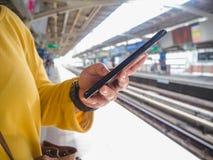 Mujer que usa tacto del finger en la pantalla del teléfono móvil en fondo del tren de cielo del BTS imágenes de archivo libres de regalías
