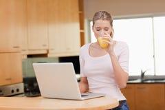 Mujer que usa un cuaderno mientras que bebe el zumo de naranja Fotografía de archivo libre de regalías